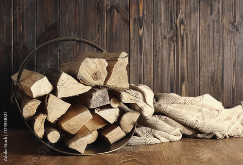 Fototapeta Basket with firewood on wooden background