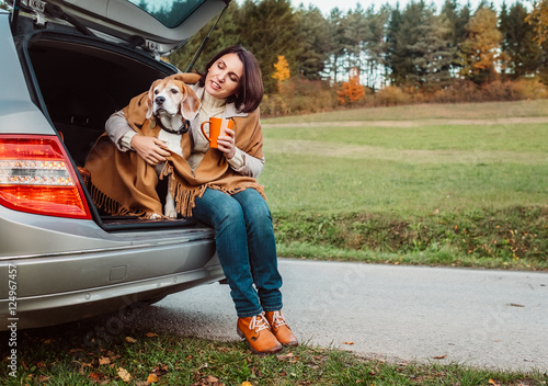 Keuken foto achterwand Vintage cars Woman with dog sit together in cat truck and warms hot tea