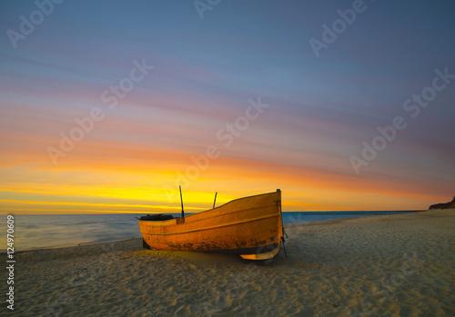 Láminas  Un barco de pesca naranja en la playa al atardecer