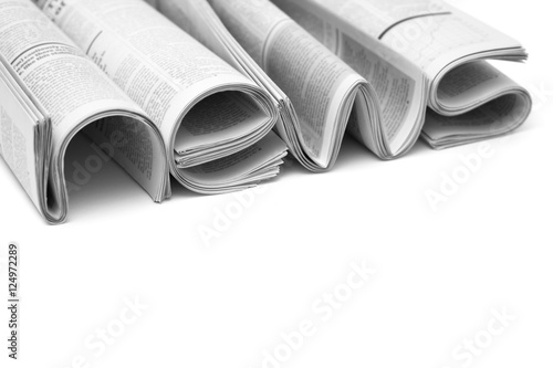 Fotografía  Stacks of modern newspapers, composed in form of word NEWS on white background