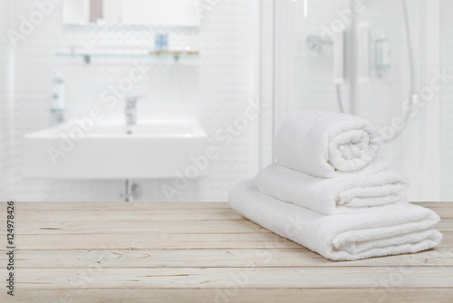 Foto  Blurred bathroom interior background and white spa towels on wood
