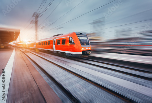 Fotografering Beautiful railway station with modern high speed red commuter train with motion blur effect at colorful sunset