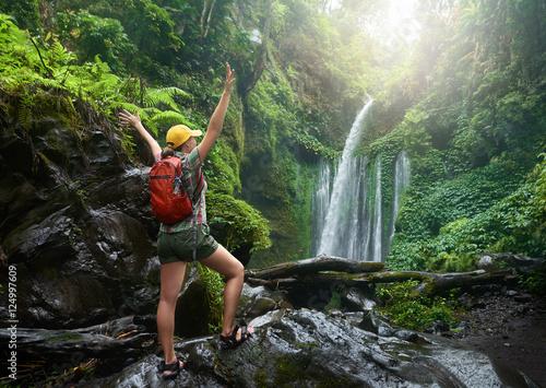 young woman backpacker enjoying view at waterfall in jungles. Slika na platnu
