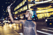 USA, New York City, smiling young woman on Times Square at night taking selfie