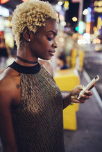 USA, New York City, Young Woman On Times Square At Night Looking At Smartphone