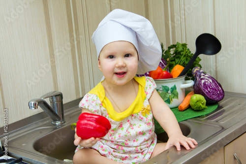 0bb09fed848 Charming little girl in a chefs hat sitting in the sink with a ladle ...