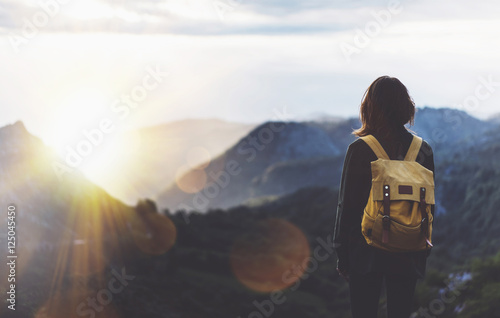 Fotografija  Hipster young girl with bright backpack enjoying sunset on peak of foggy mountain