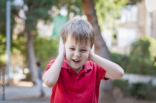 Valokuva  Stressed out little boy closed his ears and screams, stock image.