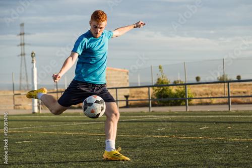 Soccer player kicking a ball at football pitch