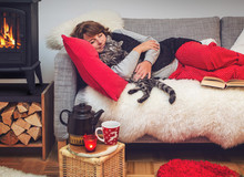 Woman Hugging Cat Lying On A Cosy Sofa Beside Fireplace
