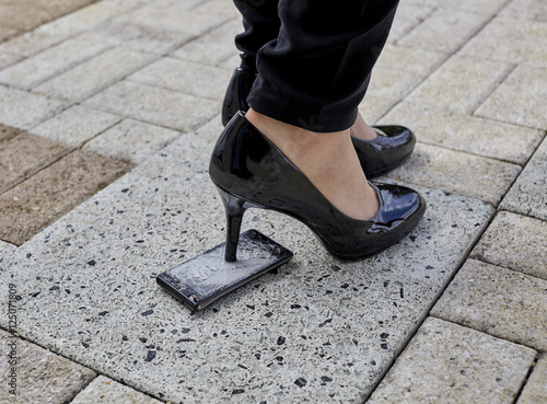 Fotografie, Obraz  Spiked Heel of a Womans Shoe stepping on a Cell Phone