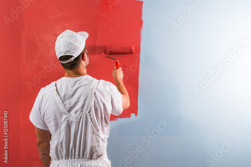 Pinturas sobre lienzo  Man painting wall with roller