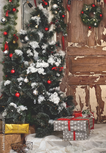Christmas tree before the door with decorations and gifts on floor