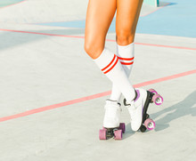 Beautiful Long-legged Girl Posing On A Vintage Roller Skates In Denim Shorts And White T-shirt In The Skate Park On A Warm Summer Evening. Part Of Body.