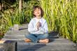 happy beautiful kid doing yoga bare feet sitting on wood
