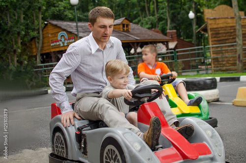 Papiers peints Attraction parc Small baby boy is enjoying driving small car
