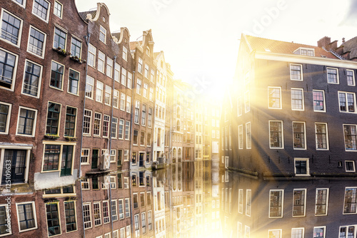 Poster Amsterdam Traditional dutch houses with sun and reflection, Amsterdam