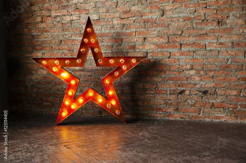 Valokuva  Decorative star with lamps on a background of brick wall