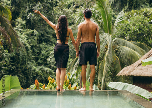 Couple at poolside looking at a view Poster