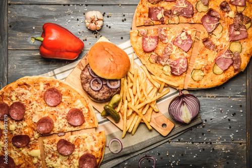 pizza and hamburger on wooden background © qwasder1987