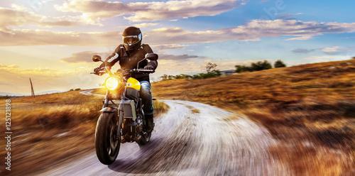 Fototapeta Motorrad fährt auf freier Landstrasse in den Sonnenuntergang