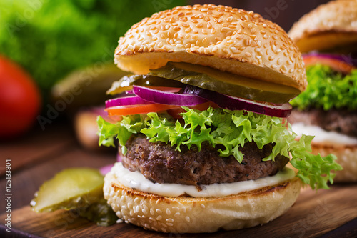 Fototapety, obrazy: Big sandwich - hamburger burger with beef, pickles, tomato and tartar sauce on wooden background.
