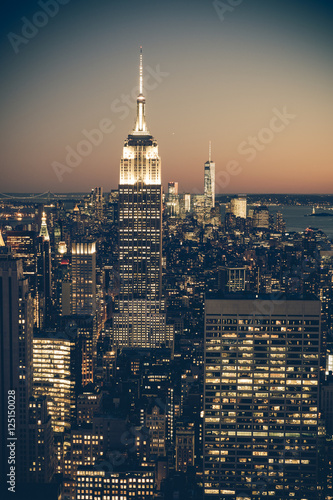 Vintage tone image of New York City at dusk with buildings and lights Poster