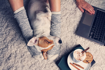 FototapetaWoman in cozy home wear relaxing at home with sleeping dog Jack