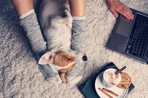 Deurstickers Ontspanning Woman in cozy home wear relaxing at home with sleeping dog Jack