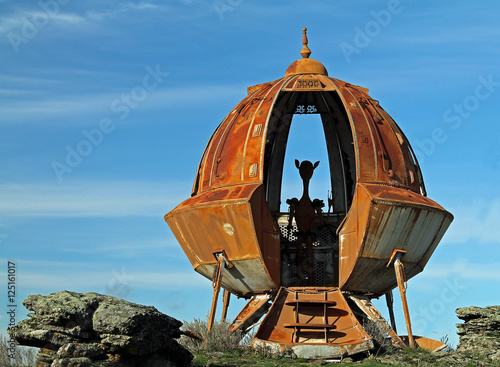 Rusty Metal UFO Against a Bright Blue Sky With Alien Silhouette Poster