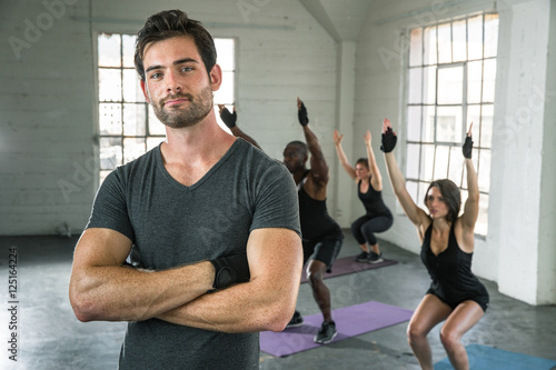 Powerful pose by professional personal trainer with arms crossed leading class exercise weight loss