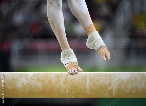 Tuinposter Gymnastiek Female gymnast on balance beam during competition