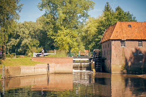 Ancient dutch water mill with tourists in sunlight. Berenschot Winterswijk.