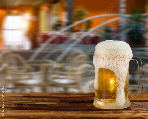 Photo sur Toile Biere, Cidre cold mug of beer with foam on the background of the street