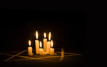 Six Burning Candles And The Star Of David Against A Black Background