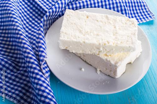 Plakat Biały ser w spodku z serwetką. Na niebieskim, drewnianym tle.