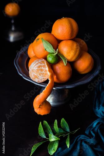 Fotografie, Obraz  mandarancio sbucciato con buccia a forma di chiocciola che pende dal vassoio