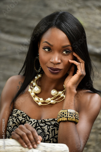 a13be40ce84 Portrait of glamour African American fashion model wearing dress and  jewelry posing pretty outdoors.