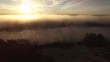 Sunrise over surreal landscape with fog over river shore, aerial view.