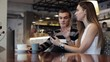 Attractive young couple talking and using smartphone at cafe