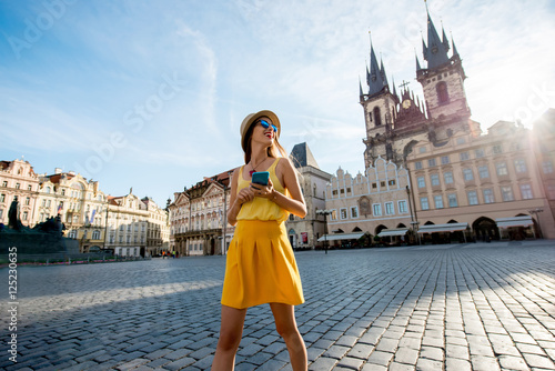 Staande foto Praag Young woman in yellow walking with smart phone on the old town square in Prague city