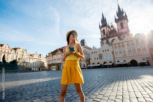 Fototapeta premium Młoda kobieta w żółtym spaceru z inteligentnego telefonu na rynku starego miasta w Pradze