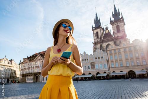 Naklejka premium Młoda kobieta w żółtym spaceru z inteligentnego telefonu na rynku starego miasta w Pradze