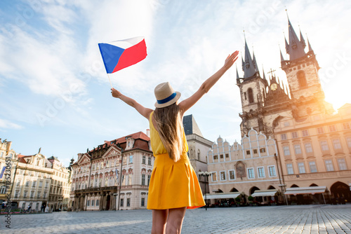 Photo  Young female tourist dressed in yellow holding czech flag on the old town square of Prague