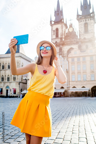 Young female tourist making self portrait on the old town square of Prague Poster