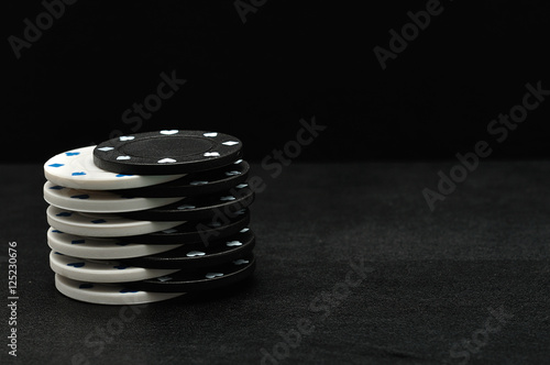 White and black poker chips on a black background плакат