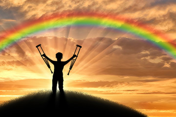 Disabled child standing with crutches on a hill sunset on the background of the rainbow.