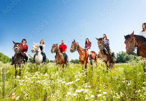Poster Horseback riding Big group of horseback riders in flowery meadow