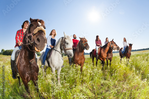Photo Stands Horseback riding Happy equestrians riding horses in summer meadow