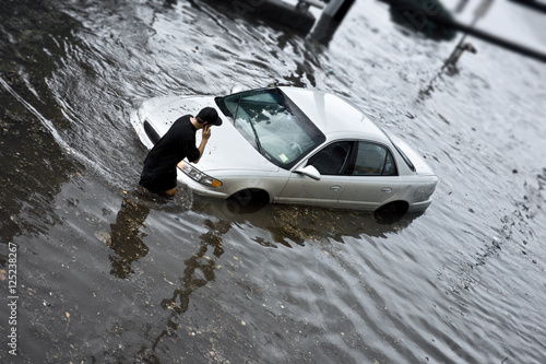 Fotografie, Obraz  Flood Insurance concept image with unrecognizable person stuck in flood waters